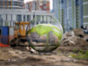 A transparent sphere with a young plant on a background of a construction site. Tractor wasteland. The new city quarter. Concept - urban environment, the destruction of green areas